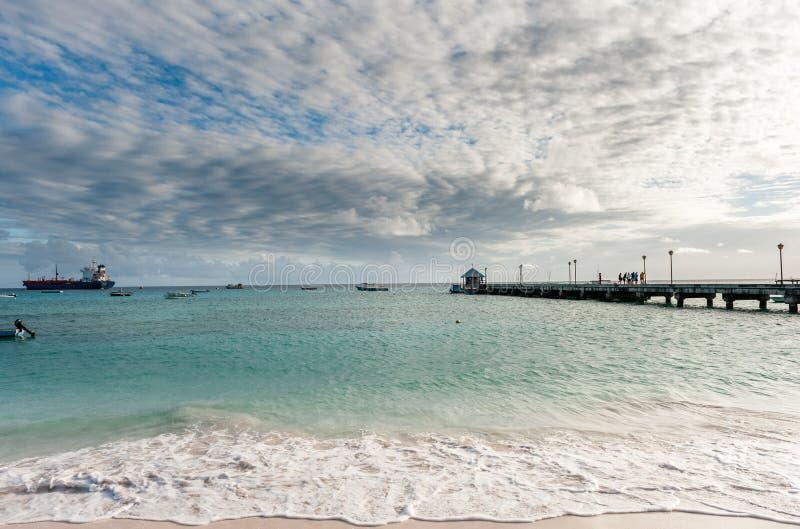 OISTINS, BARBADOS - 15 DE MARZO DE 2014: Paisaje de Miami Beach con el petrolero químico del cielo y del aceite del drama del agu imagen de archivo