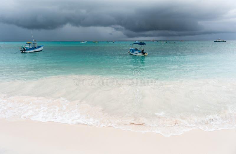 OISTINS, BARBADOS - 15. MÄRZ 2014: Miami Beach in Barbados mit bewölktem stürmischem Himmel und Yacht, Boote im Hintergrund lizenzfreie stockbilder