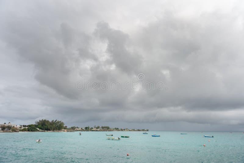 OISTINS BARBADOS - MARS 15, 2014: Miami Beach i Barbados med molnig stormig himmel och yachten, fartyg i bakgrund arkivbild