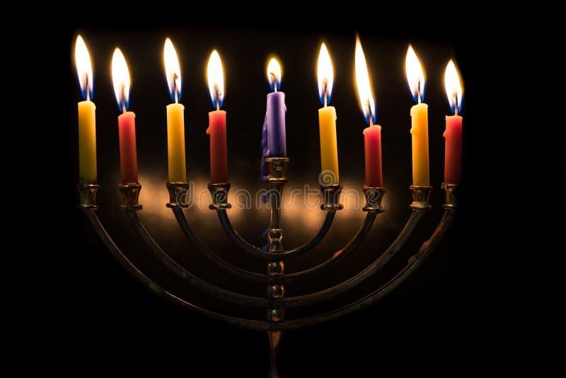 Oito velas iluminadas do Hanukkah no fundo preto fotos de stock royalty free