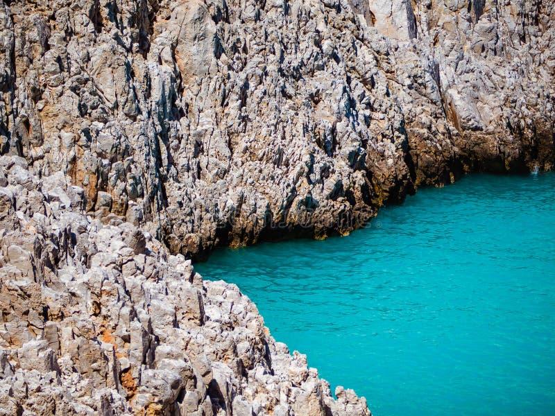 Ojämna steniga klippor precis på den avskilda stranden med sublimt blått vatten royaltyfri foto