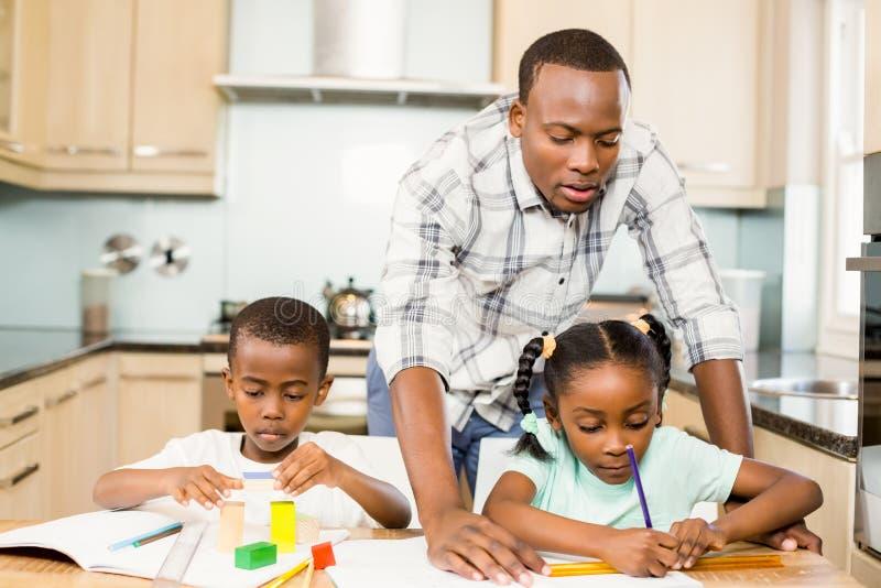 Ojców pomaga dzieci dla pracy domowej zdjęcia royalty free