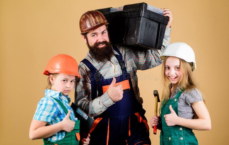 Ojca budowniczy żartuje dziewczyny Uczy córki Nieformalna edukacja Ojca dzień Siostry pomocy ojca budowniczy Nasz tata zdjęcie royalty free