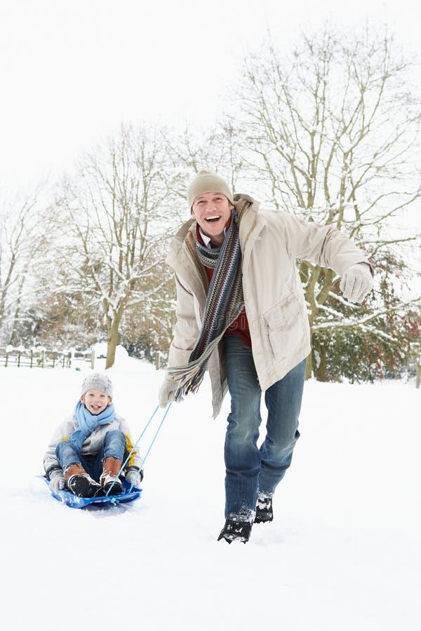 ojca ciągnięcia saneczki śniegu syn zdjęcia stock