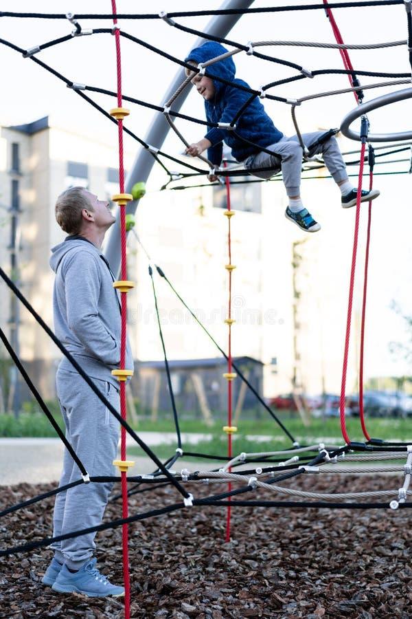 Ojca dzień ogląda troszkę chłopiec sztukę na nowożytnym Europejskim miasta boisku wesoło mężczyzna zdjęcia royalty free