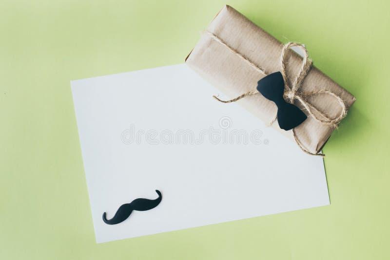 Ojca dzie? Prezenta pakunek zawijający z papierem i arkaną z dekoracyjnym krawatem na zielonym tle Copyspace fotografia stock