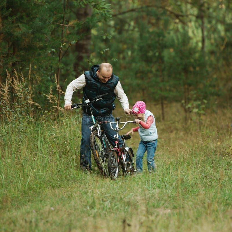 Ojca i córki jazda jechać na rowerze w lesie zdjęcie stock