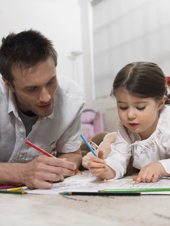 Ojca I córki kolorystyki książka Na podłoga fotografia royalty free