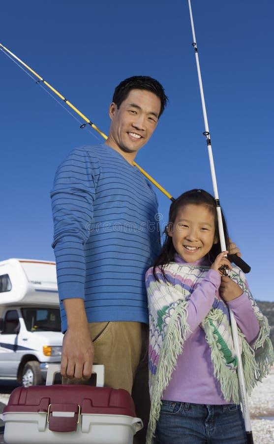 Ojca i córki mienia połowu słupy na zewnątrz RV obrazy royalty free