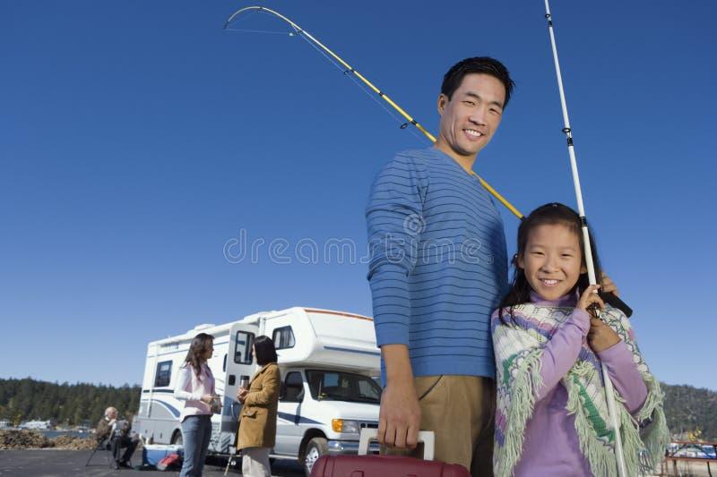 Ojca i córki mienia połowu słupy na zewnątrz RV obraz royalty free