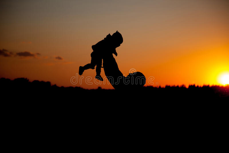 ojca i małego dziecka sylwetki bawić się przy zmierzchu niebem zdjęcia stock