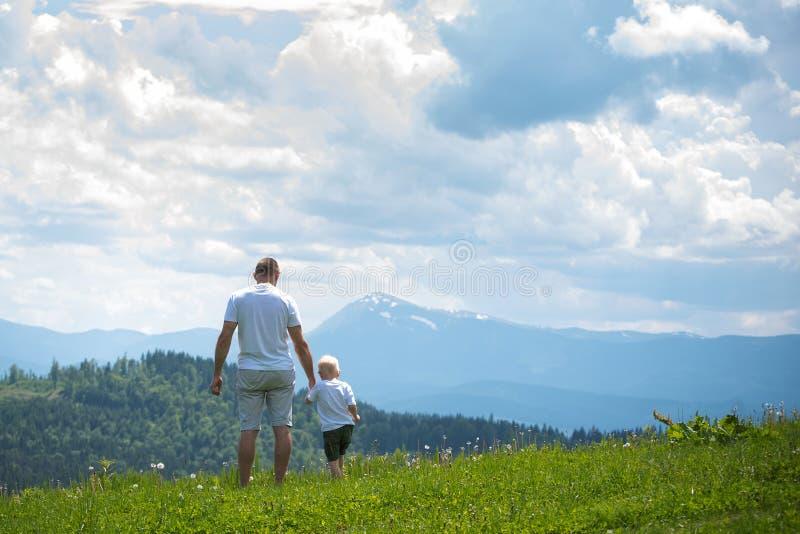 Ojca i potomstwo syna pozycja na gazonie i podziwiać górę obrazy stock