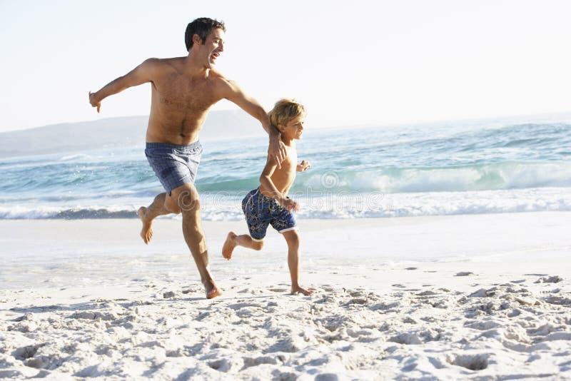 Ojca I syna bieg Wzdłuż plaży Wpólnie Jest ubranym Pływackich kostiumy obrazy royalty free