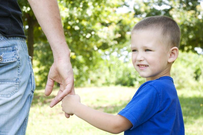 Ojca i syna mienie wręcza odprowadzenie w parku fotografia royalty free