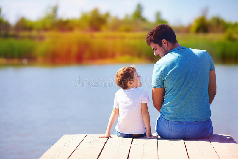 Ojca i syna obsiadanie na molu jeziorem na pogodnym letnim dniu fotografia royalty free