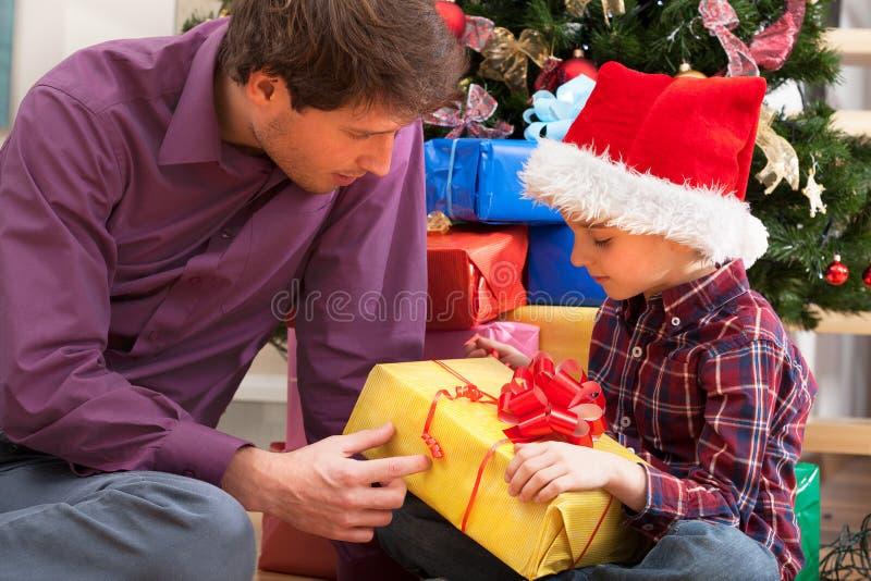 Ojca i syna obsiadanie pod choinką fotografia royalty free
