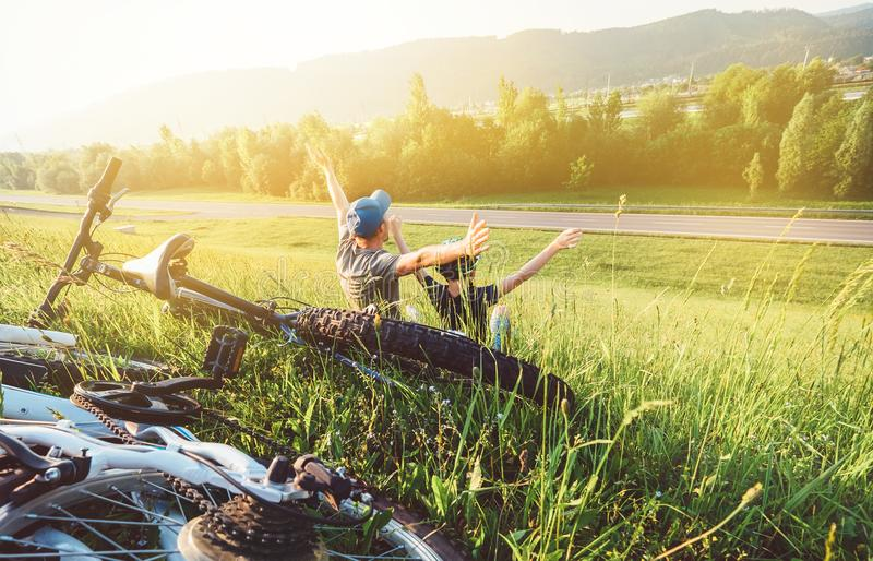 Ojca i syna odpoczynek wpólnie w zielonej trawie gdy rowerowego wa fotografia royalty free