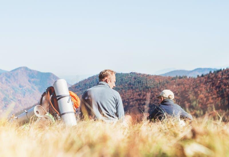 Ojca i syna podróżnicy odpoczywają wpólnie w halnej dolinie z b obrazy stock