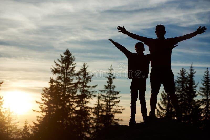 Ojca i syna pozycja na wierzcho?ku g?ra przy zmierzchem zdjęcie royalty free