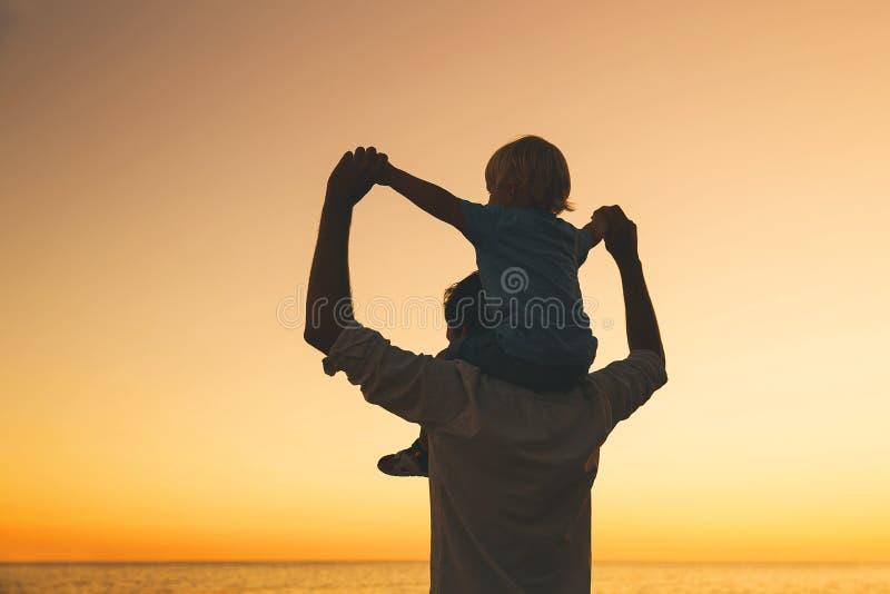 Ojca i syna sylwetki przy zmierzchem na morzu wyrzucać na brzeg obrazy royalty free