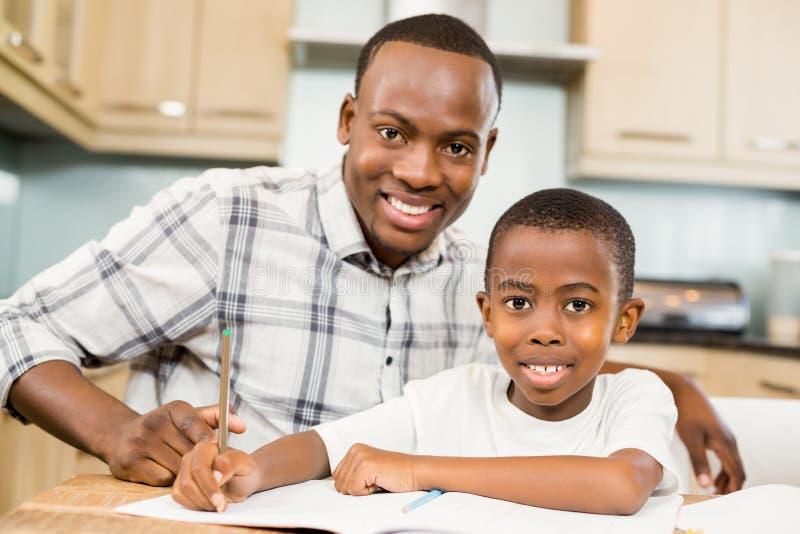 Ojca pomaga syn dla pracy domowej obraz stock