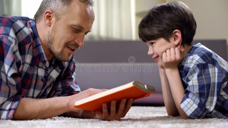 Ojca preschool czytelniczy dziecko ciekawa opowieści książka, wydaje czas wpólnie zdjęcia stock