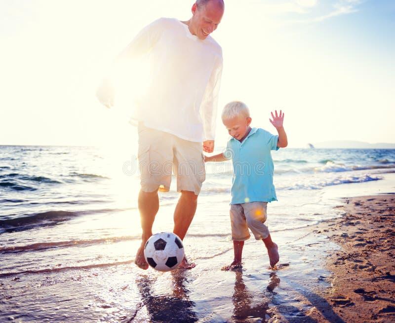 Ojca syn Bawić się piłki nożnej lata Plażowego pojęcie zdjęcie royalty free