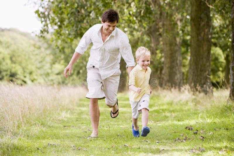 ojciec ścieżka prowadzi uśmiechniętego syna fotografia stock