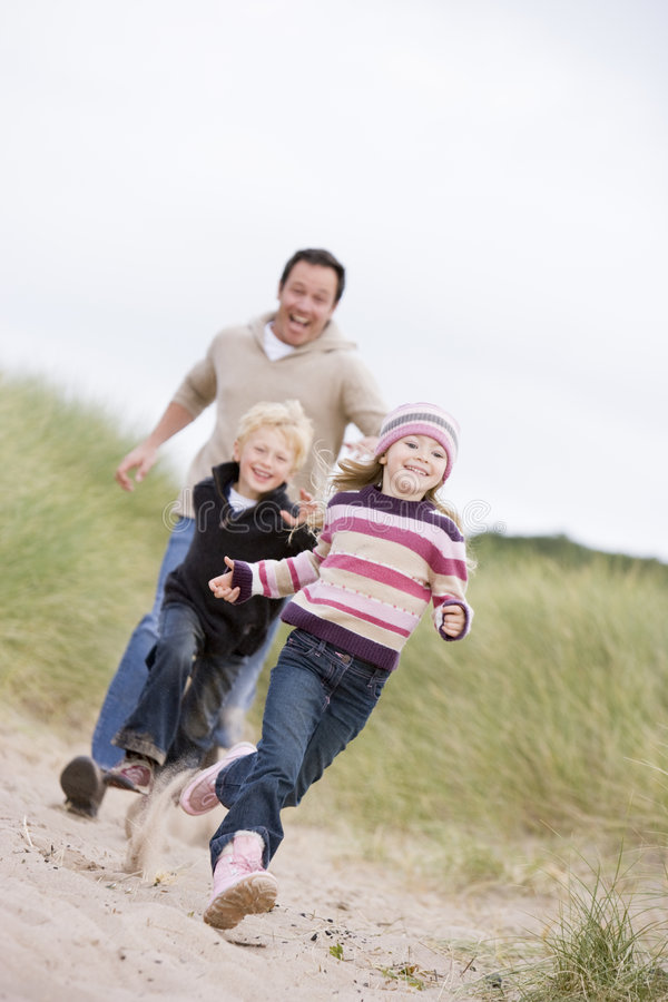 ojciec dziecka na plaży prowadzi dwa młode obraz stock