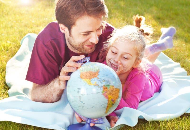 Ojciec i córka bawić się kulę ziemską w ogródzie zdjęcia royalty free
