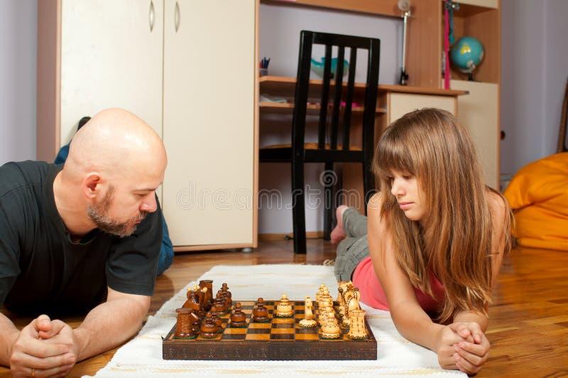 Ojciec i córka bawić się szachy zdjęcia stock