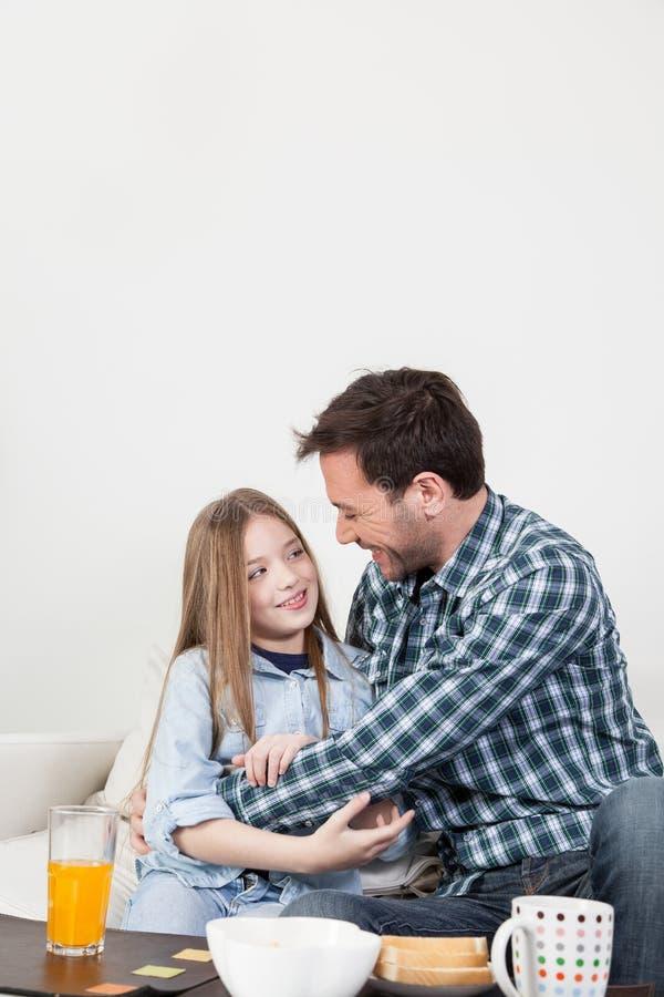 Ojciec i córka daje uściśnięciu w śniadaniu fotografia stock