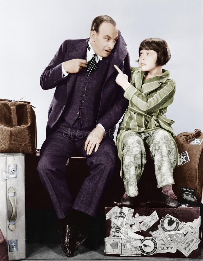 Ojciec i córka siedzi wpólnie na bagażu (Wszystkie persons przedstawiający no są długiego utrzymania i żadny nieruchomość istniej obrazy royalty free