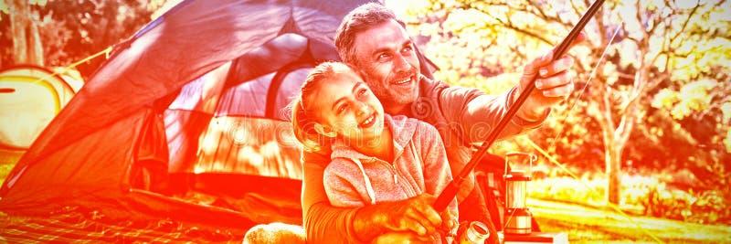 Ojciec i córka trzyma połowu prącie na zewnątrz namiotu obraz stock