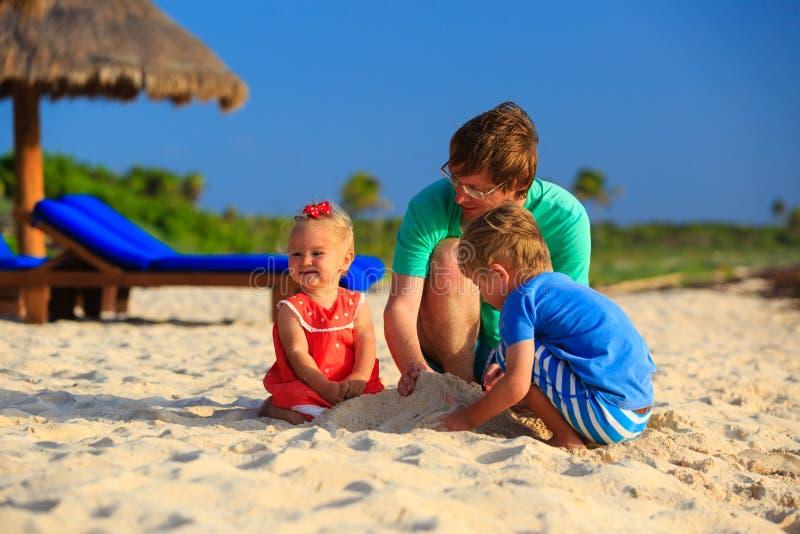 Download Ojciec I Dwa Dzieciaka Bawić Się Z Piaskiem Na Plaży Obraz Stock - Obraz złożonej z ojciec, szczęśliwy: 53791725