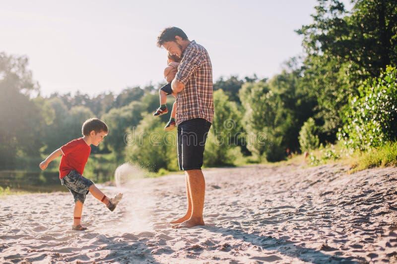 Ojciec i dwa syna ma zabawę outdoors zdjęcie stock