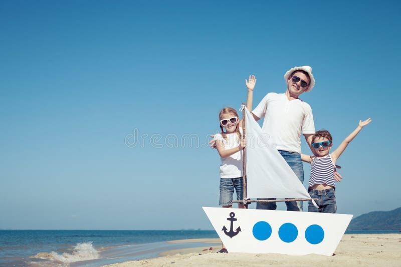 Ojciec i dzieci bawić się na plaży przy dnia czasem zdjęcie stock