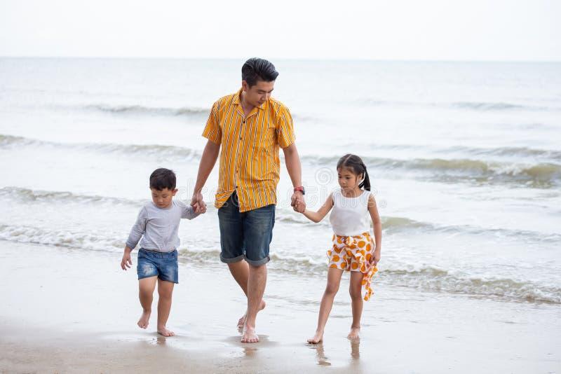 Ojciec I dzieci chodzi Na Plażowym wakacje dwa dzieciaka jeden tata fotografia royalty free