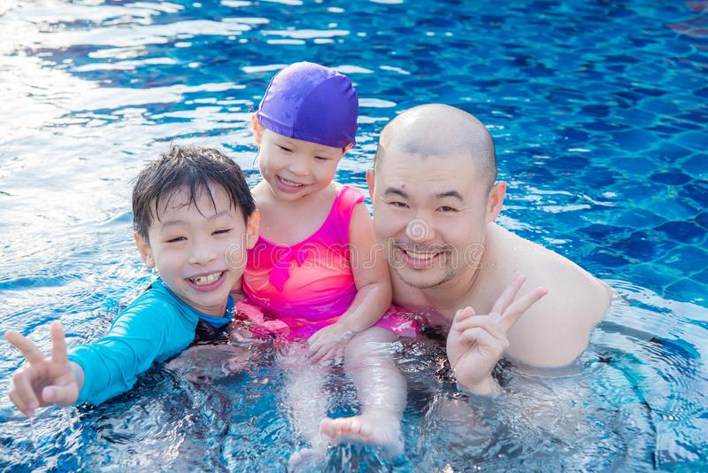 Ojciec i jego dzieci w pływackim basenie obraz stock