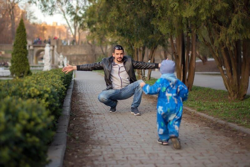 Ojciec i mały syn ma zabawę wpólnie: Mały berbeć jest gotowy obejmować jego chłopiec biega jego ojciec w wiosna parku, tata zdjęcie stock