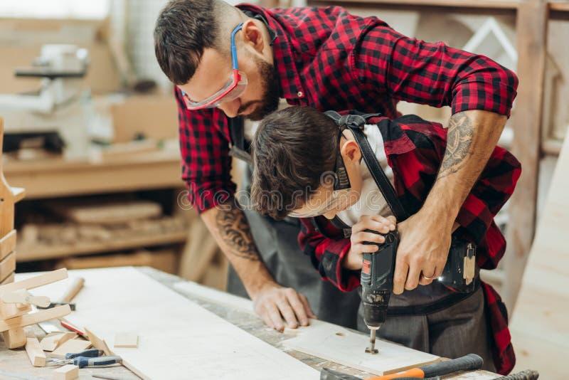 Ojciec i mały syn pracuje z świder perforacyjną drewnianą deską przy warsztatem zdjęcia stock