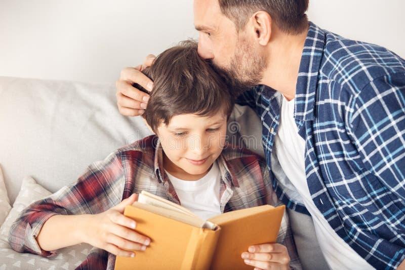 Ojciec i mały syn siedzi na kanapa taty całowania głowie chłopiec czytelnicza książka radosna w górę w domu obraz royalty free