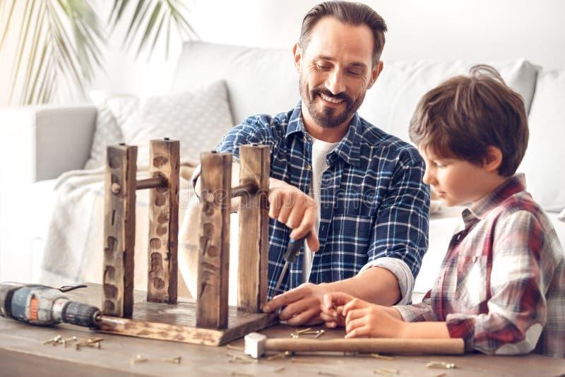 Ojciec i mały syn stoi chłopiec patrzeje taty śrubowania ciekawego gwóźdź szczęśliwego w górę w domu obraz stock