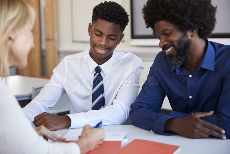 Ojciec I nastoletni syn Ma dyskusję Z Żeńskim nauczycielem Przy szkoła średnia rodziców wieczór zdjęcia royalty free