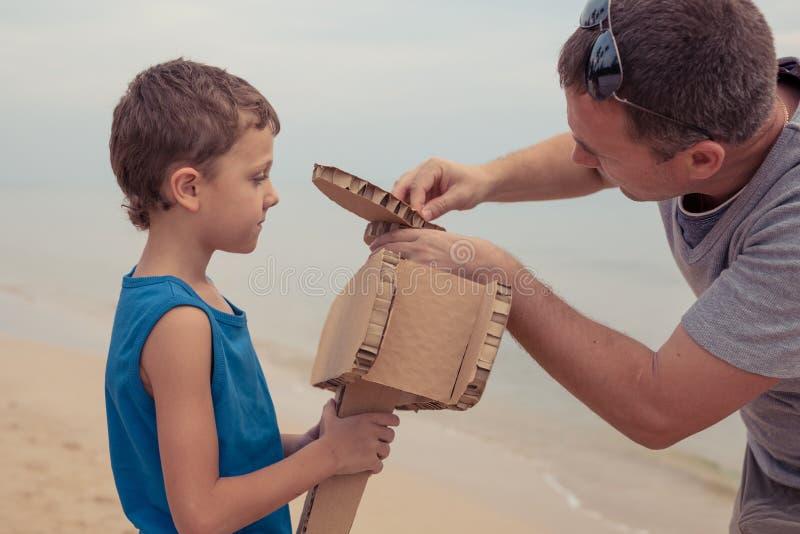 Ojciec i syn bawiący się kartonowym samolotem zabawkowym zdjęcia royalty free