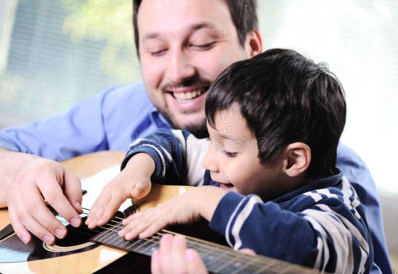 Ojciec i syn bawić się gitarę obraz royalty free