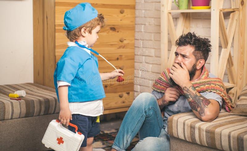 Ojciec i syn bawić się jako część terapii lekarkę z chłopiec mienia stetoskopem i słuchanie obraz royalty free