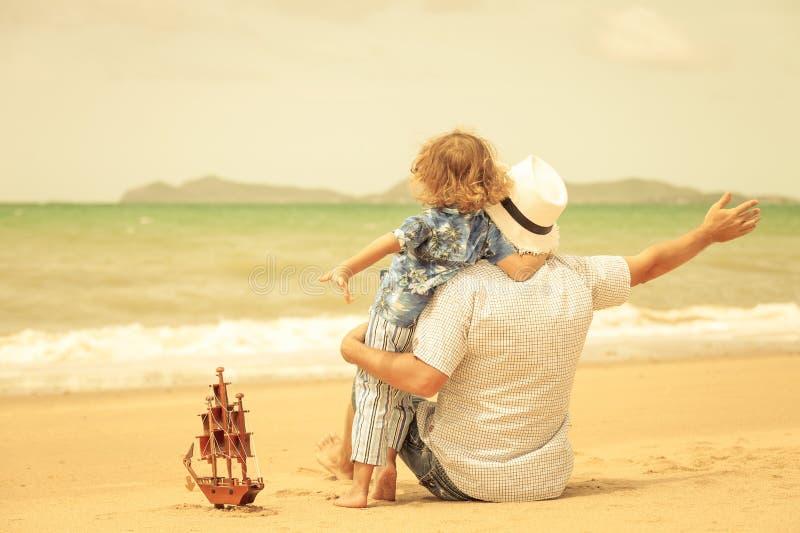 Ojciec i syn bawić się na plaży przy dnia czasem obraz stock