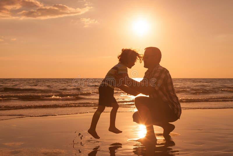 Ojciec i syn bawić się na plaży przy zmierzchu czasem zdjęcie royalty free