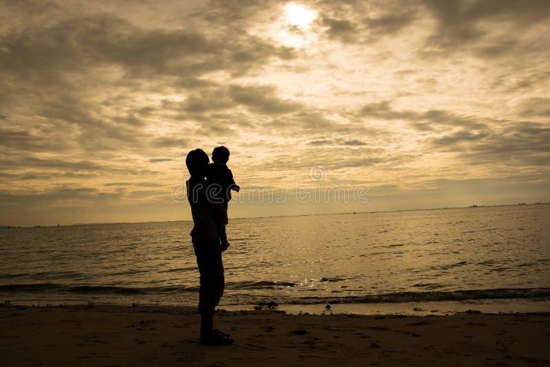 Ojciec i syn bawić się na plaży przy zmierzchu czasem Pojęcie życzliwa rodzina zdjęcia stock